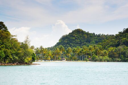 Tropical sea and sandy beach with palm trees and bungalows on the island on horizon at the Koh Chang island, Thailand. Stock Photo