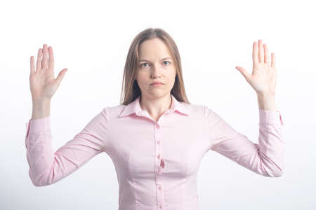 It was not me, I am innocent. Portrait of woman raising palms up in surrender and staring at camera with clueless anxious expression, standing against white background