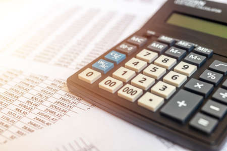 Document - Personal or corporate Budget with a calculator and documents with table of digits on office table, financial accounting concept