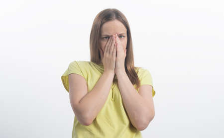 Shocking news. Surprised and calm woman covers her mouth, close-up, isolated on a white background, woman pretending to be shocked and surprised