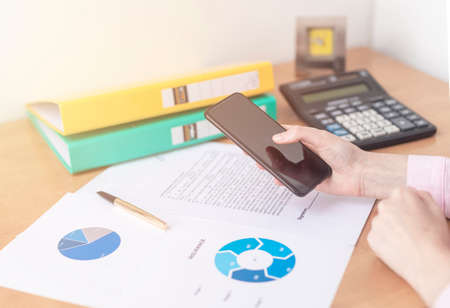Close up female hands holding smart phone while connecting to wireless, businessman using technology sitting at wooden desk, people and modern devices everywhere, flare sun light, documents paper