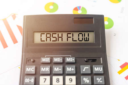 word cash flow on calculator on financial documents with charts diagrams background, business cashflow