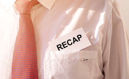RECAP word on white card paper sheet in pocket of a businessman. recap concept. red and white paper Stock Photo