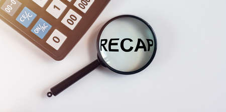 Recap word inscription through magnifying glass on white table with calculator, review in finance, summary concept.