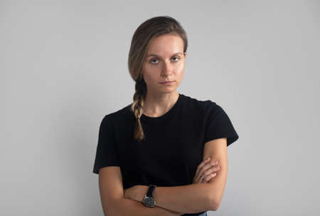 caucasian woman with braid over gray studio background. Bothered and annoyed european female student rolling eyes and sighing, standing with crossed arms, being bored and fed up of nonsense talks.