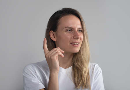 Closeup portrait of young woman, finger on top, daydreaming something serious and upsetting, isolated on gray background. Human facial expressions, emotions, feelings, signs, symbols. Archivio Fotografico