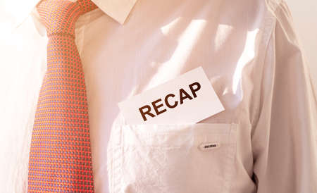 RECAP word inscription on paper card in pocket of male white shirt with red tie, close up.