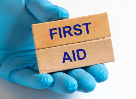 FIRST AID text inscription on wooden blocks in doctor hand in blue gloves over white table.