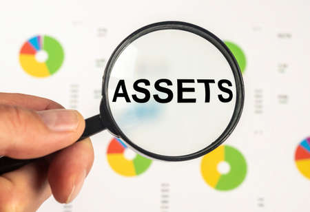 word Assets on paper through magnifying glass on office table with charts. Financial accounting. Money concept.