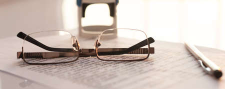 Stamping contract, spectacles glasses, pen and stamp on contract on white glossy table. banner
