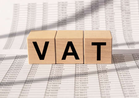 VAT text, Value Added Tax, inscription on cube blocks on financial background.