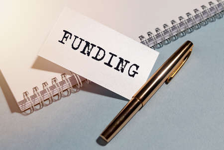 FUNDING word written on paper with notebook with pen.