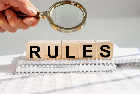 Rules Word In Wooden Cube on office table through magnifying glass.