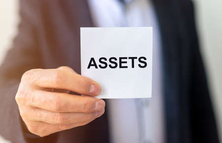 word Assets on paper in businessman hand Financial accounting. Money concept, close up