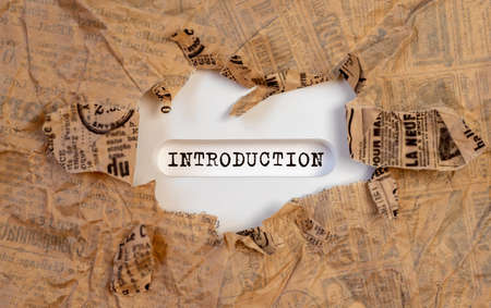Closeup of a handwritten word Introduction on white table through torn paper.