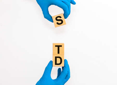 STD, Sexually transmitted infections, acronym text on wooden cubes in doctor gloves over white background.