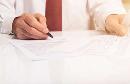Contract signing concept. Businessman hand with pen over document with copy space available. Archivio Fotografico
