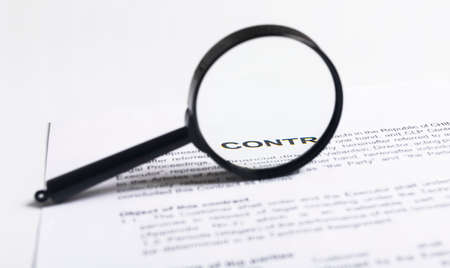 Magnifying Glass over contract, inspection of documents agreement concept.