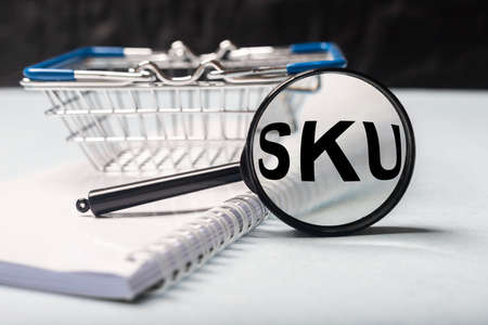 SKU acronym, Stock Keeping Unit through magnifier on office table with shopping basket blurred close up, warehouse and trading concept