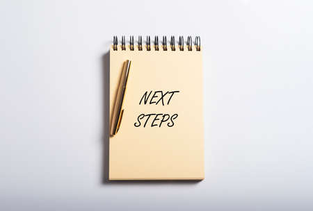 next step phrase on yellow notebook on blue table with golden pen, top view