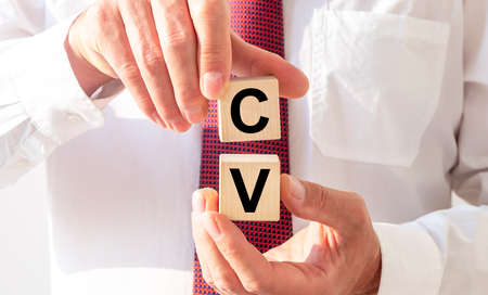 CV word written on cube blocks in hands of recruiter or applicant in shirt and tie