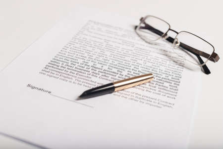 Contract signing concept. golden pen and spectacles over document contract closeup