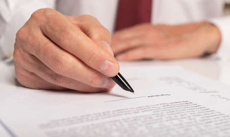 Contract signing concept. Businessman hand with pen over document closeup.
