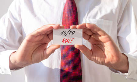 80 20 Rule concept inscription on white paper in businessman hands.