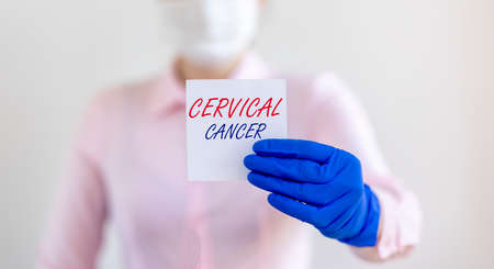 Cervical cancer inscription on paper note in doctor hand.