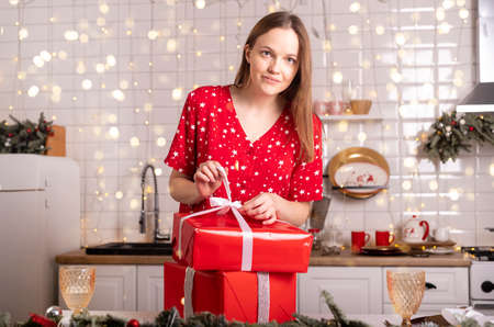 Happy young caucasian woman glad with unpacking christmas gifts or xmas presents in wrapped red boxes. New year at home in pyjamas in kitchen.