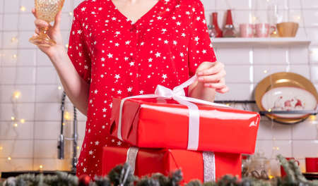 Cropped woman unpacking christmas gifts or xmas presents in wrapped red boxes. New year at home in pyjamas in kitchen with wineglass.