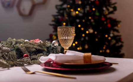 Wineglass and plates on served or setted table for christmas celebration. Empty dininng room with fir tree blurred on background. Magic Xmas night.