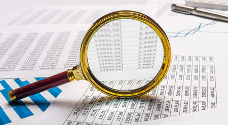 Business financial analysis and research concept. Magnifier on documents.