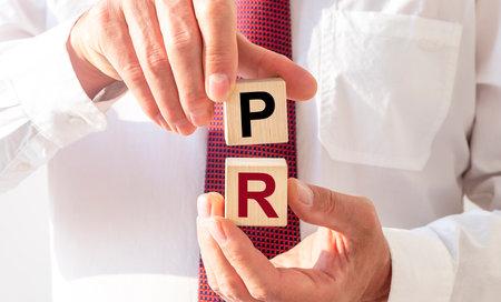 PR acronym inscription on cubes. Public relations concept.