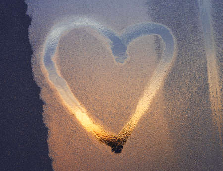 Heart drawn on frosty or foggy window on sunset.