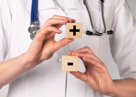 Plus and minus signs on wooden cubes. Medical concept.
