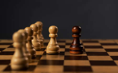 Single black pawn against group of white on chess board. Concept of unique, different, individual