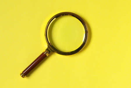 Trendy colored yellow background with magnifying glass