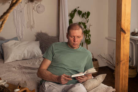 Mature man reading book in modern trendy cozy interior with plant in evening, alone