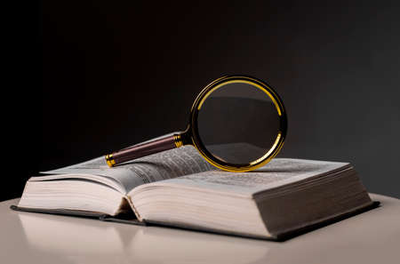 Open book closeup with turning pages and magnifying loupe. Textbook in hard cover on table. Studying and research concept.