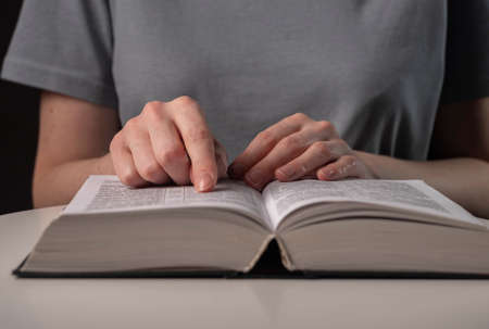 Female student hands close up, pointing on text in book or textbook, searching for information and reading at night.