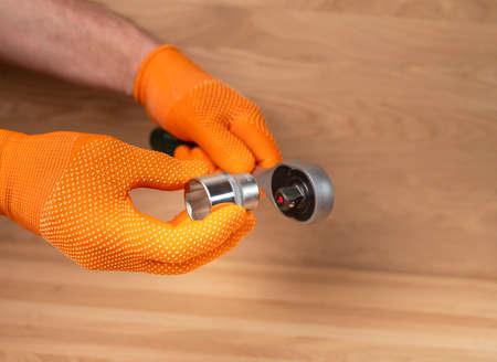 Male hand in building glove with socket ratchet handle and metal steel hex socket, hexagon metal head. Industrial metal tool, close up.