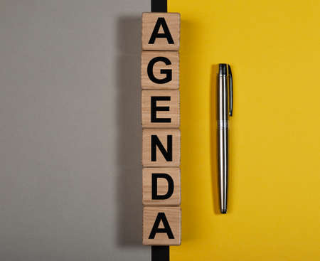 Agenda word on wooden cubes on yellow and gray background.