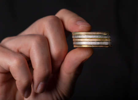 Male fingers holding stack of coins. Concept of money laundry, black false accounting. Banque d'images