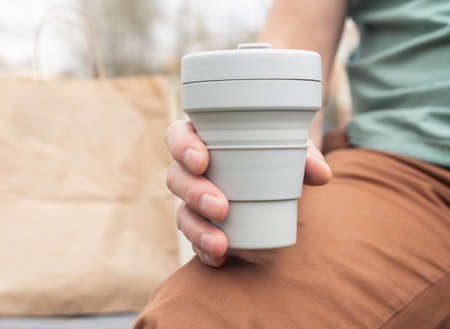 Collapsible cup for takeaway coffee or tea. Male hand with sustainable silicon mug. Eco-friendly life. Stock fotó