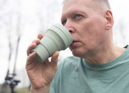 Mature man holding eco reusable cup or silicon mug and drinking takeaway coffee.