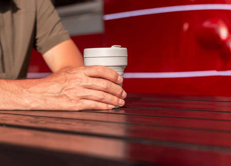 Male hands holding reusable takeaway eco coffee cup in hands over wooden street table on court with background with copy space for text.