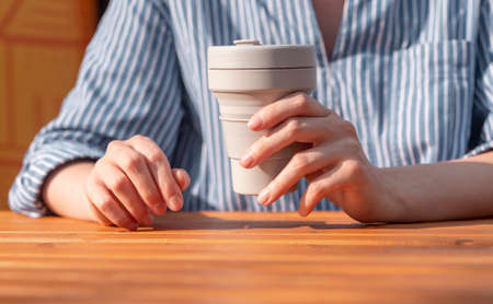 Woman hands closeup holding reusable silicon takeaway eco coffee cup in hands over wooden table. 写真素材