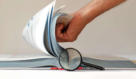 Technical book with turning pages and magnifier. Engineer research.
