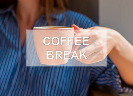 Coffee break inscription on photo with hand holding coffe cup.